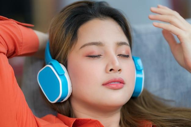 Портрет молодой красивой женщины, наслаждающейся музыкой с улыбающимся лицом, сидящей у окна в творческом офисе или кафе