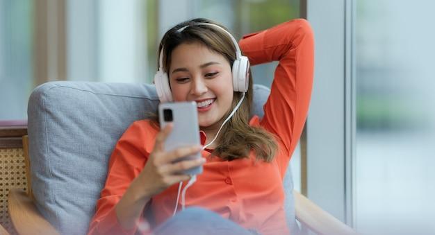 창조적 인 사무실이나 카페에서 창 근처에 앉아 웃는 얼굴로 음악을 즐기는 젊은 아름 다운 여자의 초상화