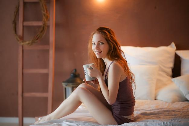 若い美しい女性の肖像画彼女の両手一杯のコーヒー彼女の白い寝室で朝の寒い冬時間。寒い冬のメイクライフスタイルコンセプトで幸せな陽気なリラックス。