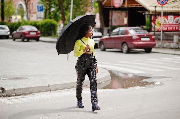 黒い傘を押しながら横断歩道を歩く若い美しい女性の肖像画