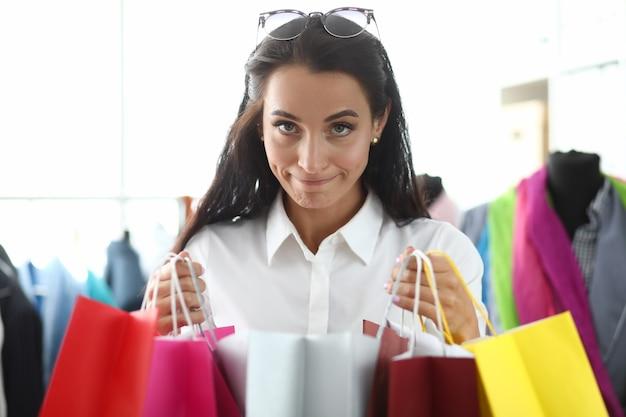 Портрет молодой красивой женщины, держащей разноцветные сумки с покупками в магазине. шопоголизм как понятие психического расстройства