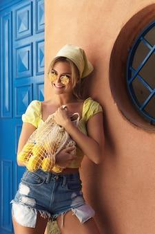 新鮮なレモンがたくさん入ったネットバッグを保持している若い美しい女性の肖像画