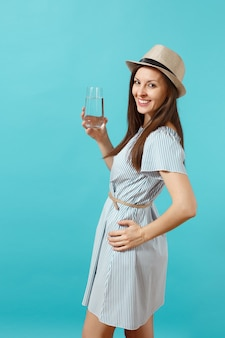 파란 드레스를 입은 젊은 미녀의 초상화, 모자를 들고 파란 배경에 격리된 유리에서 맑고 깨끗한 물을 마시고 있습니다. 건강한 생활 방식, 사람들은 진실한 감정 개념입니다. 공간을 복사합니다.