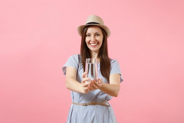파란 드레스를 입은 젊은 미녀의 초상화, 모자를 들고 분홍색 배경에 격리된 유리에서 맑고 깨끗한 물을 마시고 있습니다. 건강한 생활 방식, 사람, 진실한 감정 개념. 복사 공간