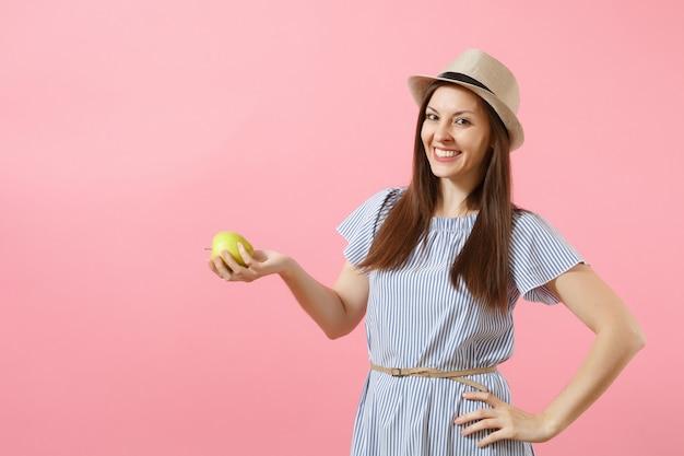 파란 드레스를 입은 아름다운 젊은 여성의 초상화, 여름 밀짚 모자를 들고 분홍색 배경에 격리된 신선한 녹색 사과 과일을 먹고 있습니다. 건강한 생활 방식, 사람, 진실한 감정 개념. 공간을 복사합니다.