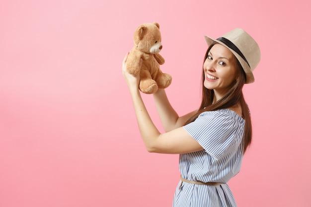 青いドレス、ピンクの背景で隔離のテディベアぬいぐるみを保持している夏の麦わら帽子の若い美しい女性の肖像画。人々、誠実な感情、ライフスタイルのコンセプト。広告エリア。スペースをコピーします。