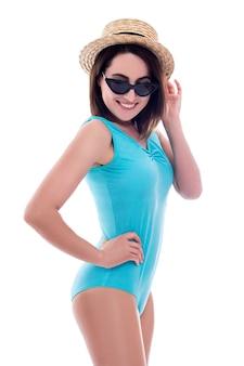 Портрет молодой красивой женщины в синем купальнике и соломенной шляпе, изолированные на белом фоне