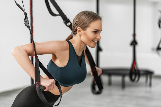 Портрет молодой красивой женщины в спортивной одежде, тренирующей руки с ремнями для фитнеса trx, в тренажерном зале, делая отжимания