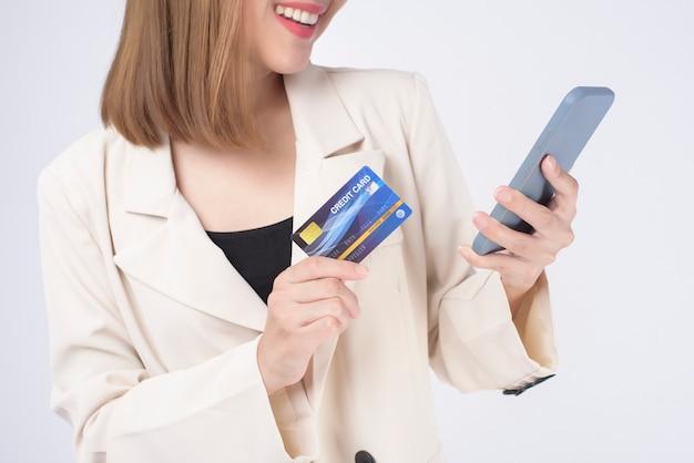Портрет молодой красивой женщины в костюме, держащей кредитную карту на белом фоне в студии