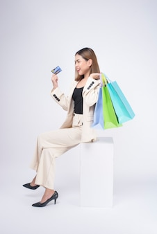 スタジオで白い背景の上にクレジットカードを保持しているスーツの若い美しい女性の肖像画
