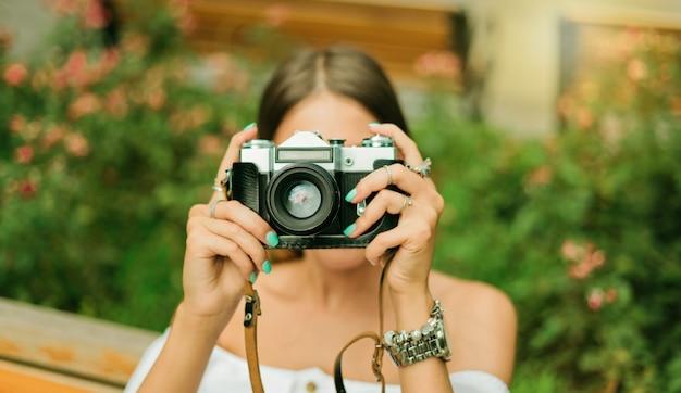 레트로 카메라와 함께 여름 옷에서 젊은 아름 다운 여자의 초상화