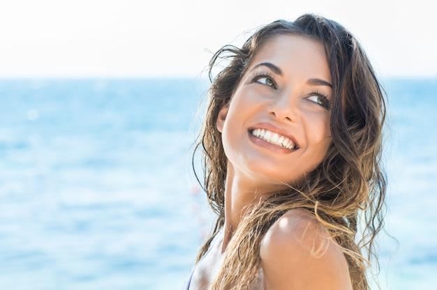 夏のビーチで笑っている若い美しい女性の肖像画