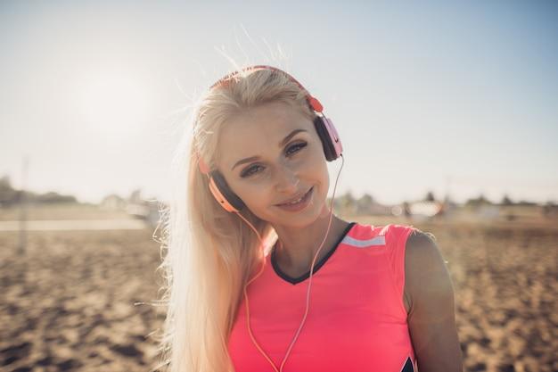 ビーチで音楽を聴く若い美しい女性の肖像画。カメラを見てイヤホンで笑顔の金髪女性の顔を閉じます。ビーチで実行して音楽を聴いている女の子。