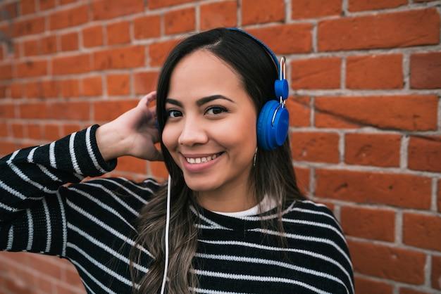 거리에서 파란색 헤드폰으로 음악을 듣고 젊은 아름 다운 여자의 초상화.