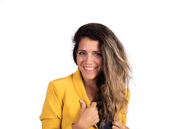 カメラを見て、白い背景のスタジオで笑っている若い美しい女性の肖像画。