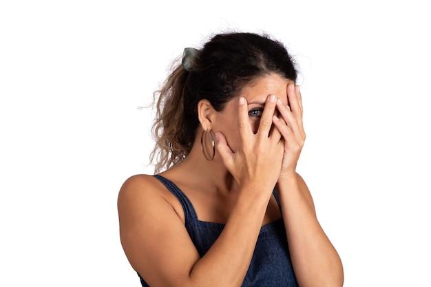 Портрет молодой красивой женщины, выглядящей застенчивой, прячась за ее рукой и улыбаясь в студии на белом фоне.