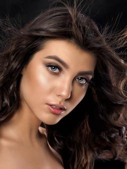 暗い背景の上の若い美しい女性の肖像画。淡褐色と夏のメイク。