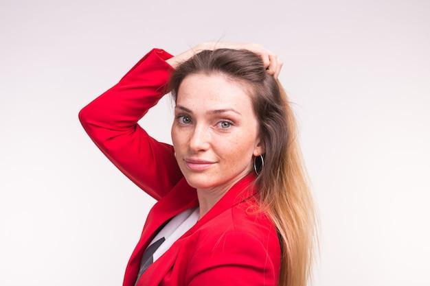 上の手で赤いスーツでポーズをとって若い美しい女性の肖像画。