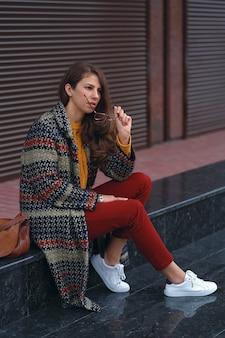 ヨーロッパの街の通りでポーズをとって、眼鏡をかけ、スタイリッシュなコート、赤いズボン、オレンジ色のセーター、白いスニーカー、茶色の革のバッグを身に着けている若い、美しい女性の肖像画。