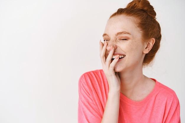 白い壁の上の顔に触れて目を閉じて笑っている若い美しい女性の肖像画。フェイシャルトリートメント。美容美容とスキンケア