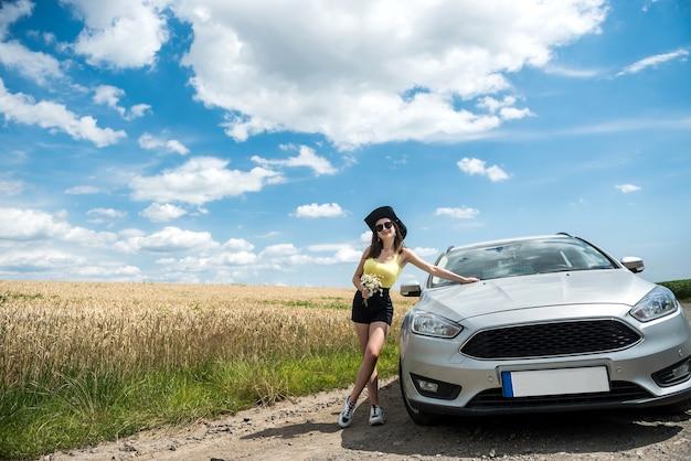 시골도에서 그녀의 차 근처에 서 있는 젊은 아름 다운 여자의 초상화. 완벽한 여름 여행을 꿈꾸다