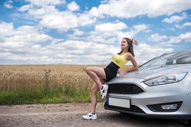 田舎道で彼女の車の近くに立っている若い美しい女性の肖像画。夏の完璧な旅行を夢見てください