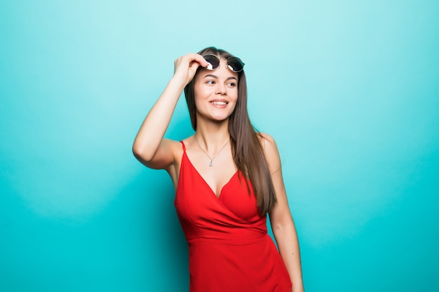 若い美しい女性の肖像画、スタイリッシュな赤いドレス、ファッショントレンド、青い壁のサングラス