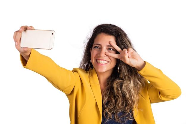 스튜디오에서 고립 된 그녀의 휴대 전화로 selfie를 복용 젊은 아름 다운 여자의 초상화.