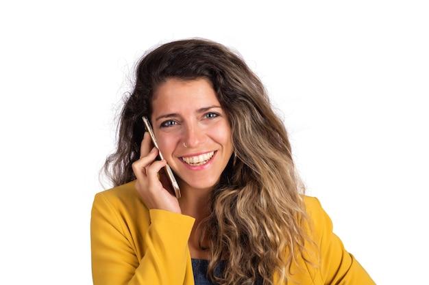スタジオで電話で話している若い美しい女性の肖像画。孤立した白い背景。コミュニケーションの概念。