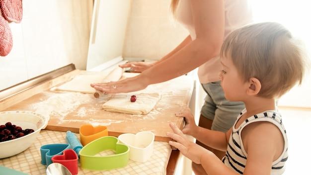 집에서 부엌에서 쿠키를 만들고 파이를 굽는 어린 아이를 가르치는 젊은 아름다운 여성의 초상화