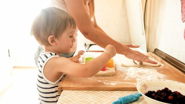Портрет молодой красивой женщины обучает своего маленького мальчика делать печенье и выпекать пироги на кухне дома