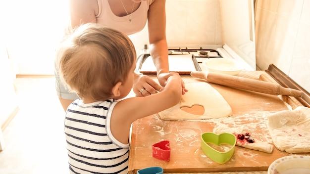 自宅のキッチンでクッキーを作ってパイを焼く彼女の小さな子供の男の子を教える若い美しい女性の肖像画