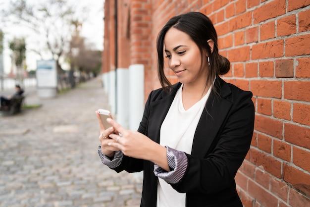 通りで屋外に彼女の携帯電話を使用して若い美しい女性の肖像画。都市とコミュニケーションの概念。