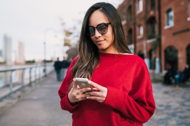 通りの屋外で彼女の携帯電話を使用して若い美しい女性の肖像画。