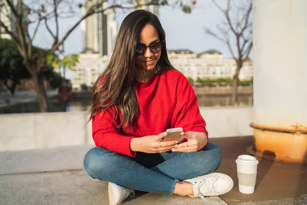屋外に座っている間彼女の携帯電話を使用して若い美しい女性の肖像画。