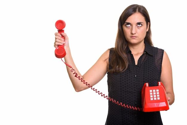 Портрет молодой красивой женщины, использующей старый телефон