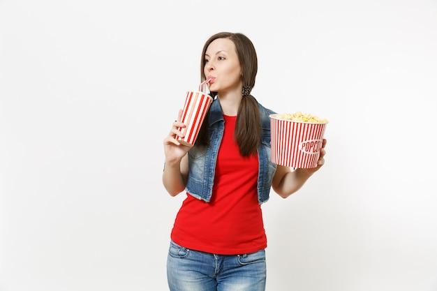 영화 영화를 보고, 팝콘 양동이를 들고, 흰색 배경에 격리된 복사 공간을 옆으로 바라보며 플라스틱 컵에 소다 또는 콜라를 마시는 젊은 아름다운 여성의 초상화. 영화 속 감정