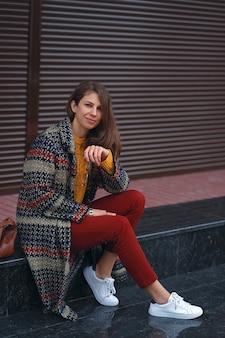 ヨーロッパの街の通りでポーズをとって、スタイリッシュなコート、赤いズボン、オレンジ色のセーター、白いスニーカー、茶色の革のバッグを身に着けている若い、美しい女性の肖像画。