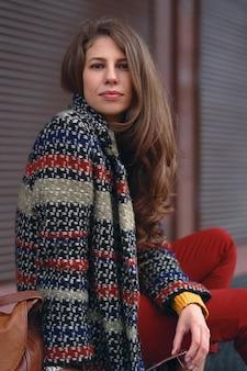 ヨーロッパの街の通りでポーズをとって、スタイリッシュなコート、赤いズボン、オレンジ色のセーター、茶色の革のバッグを身に着けている若い、美しい女性の肖像画。