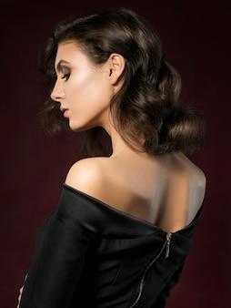 Портрет молодой красивой женщины в черном вечернем платье позирует на темно-красном фоне
