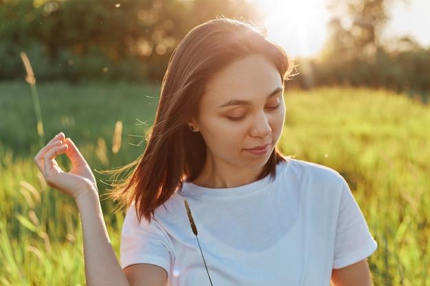 Портрет молодой красивой женщины в белой повседневной футболке с темными волосами, позирующей на закате в поле или лугу, глядя с мечтательным выражением лица, наслаждаясь закатом и природой.