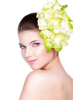 健康できれいな肌を持つ若い美しい女性の肖像画。顔の近くに花を持つきれいな女性-白い背景で隔離。