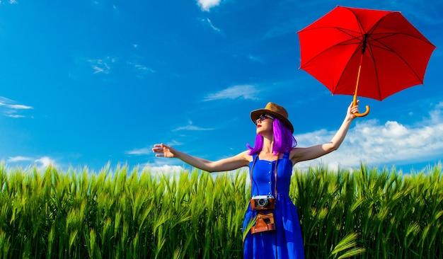 フィールドでカメラと赤い傘を持つ若い美しい女性の肖像画