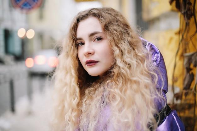 屋外で巻き毛の金髪の若い美しい女性の肖像画。美容、ファッションのコンセプト。ストリートスタイル。ボケ味の背景