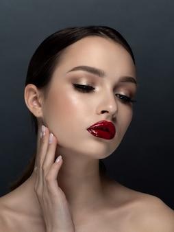 Портрет молодой красивой женщины с вечером составляет касаясь ее лица. макияж, мириться