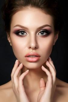 夕方の若い美しい女性の肖像画は、黒い背景の上に彼女の顔に触れて構成します。