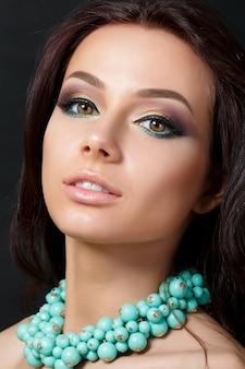 저녁 아름 다운 젊은 여자의 초상화는 파란색 목걸이 입고 메이크업. 모델 포즈. 아이 라이너로 스모키 눈. 클래식 메이크업 개념.