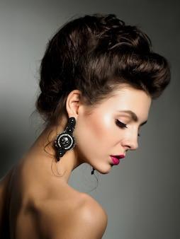 イブニングメイクと髪型の若い美しい女性の肖像画。