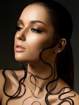 패션 황금 메이크업과 젖은 머리와 아름 다운 젊은 여자의 초상화. 아름다움.