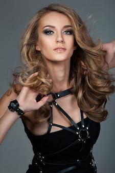 革バンドと黒のドレスを着て飛んで髪を持つ若い美しい女性の肖像画